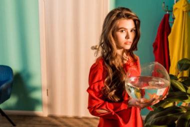 Девушка в красном платье с круглым аквариумом и золотой рыбкой.